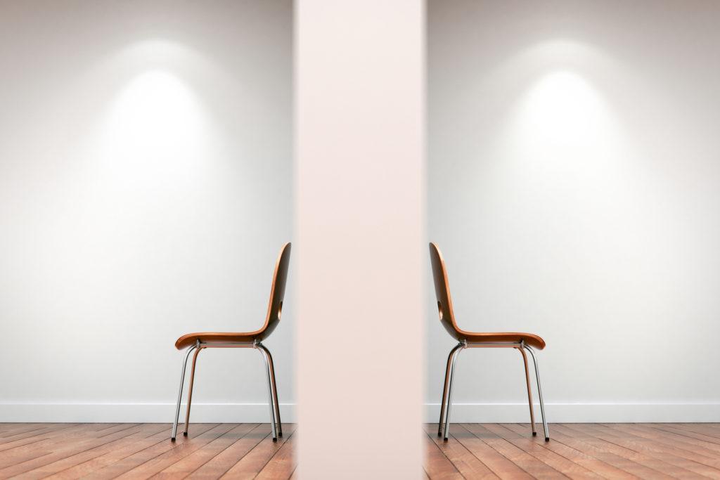 zwei Stühle getrennt durch eine wand